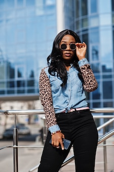 선글라스를 쓴 힙스터 아프리카계 미국인 소녀, 표범 소매가 달린 청바지 셔츠, 휴대전화를 들고 거리에서 현대적인 사무실 건물에 맞서 포즈를 취합니다.