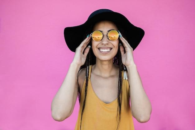 분홍색 배경으로 야외에서 카메라를 보며 웃고 있는 힙스터 아프리카 소녀 - 얼굴에 초점