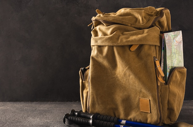 Hipster backpack with map and trekking hiking stick. hiking in the mountains concept