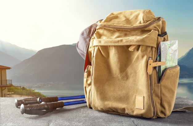 Hipster backpack with map and trekking hiking stick on the table against the mountains. hiking in the mountains concept