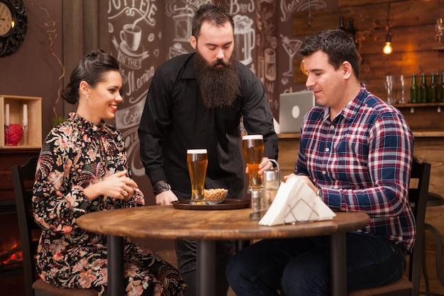 Barista hipster che dà l'ordine alla bella giovane coppia. grande pub.