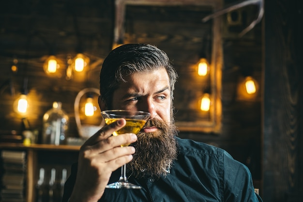 マティーニやお酒を持った流行に敏感なバーマン。スーツを着て酒を飲むひげを生やした男。飲み物とお祝いパーティーのコンセプト。デグステーションとテイスティング。