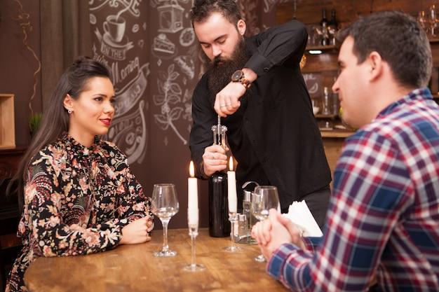 힙스터 수염이 있는 바텐더가 고객을 위해 와인 한 병을 여는 것입니다. 그들은 빈티지 힙스터 펍이나 레스토랑에 있습니다.