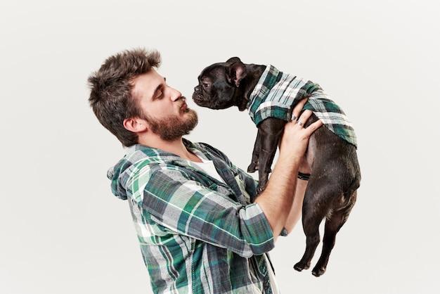 Hipster бородатый парень, держащий и обнимающий красивую собаку французского бульдога с любовью и играющую с ним, у белой стены