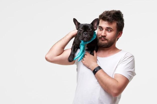 Hipster бородатый парень с любовью обнимает и обнимает красивую собаку французского бульдога и играет с ним
