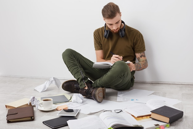 Hipster bearded guy with tattooes, wears casual clothes and boots being busy with studying
