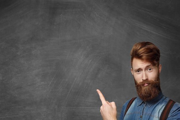 流行に敏感なひげを生やした男は、アイデアを持ち、指を上に向け、面白がった表情で見て、プロモーションコンテンツのコピースペースがある空白の黒板の右下隅に孤立して立っています。