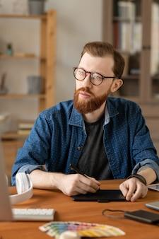Hipster 수염 남자 테이블에 앉아 시각적 솔루션을 생각하는 동안 디지타이저 태블릿을 사용하여 안경