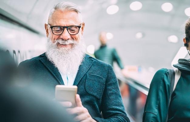 Hipster 수염 난 남자 쇼핑몰 엘리베이터에서 모바일 스마트 휴대 전화를 사용 하여