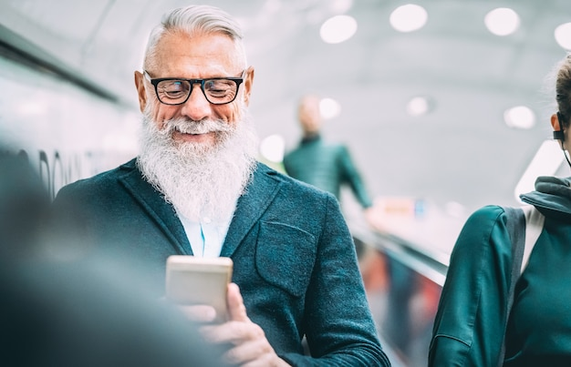 Hipster bearded man using mobile smart phone at shopping mall elevators