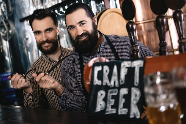 Hipster bearded men in atmosphere pub craft beer.