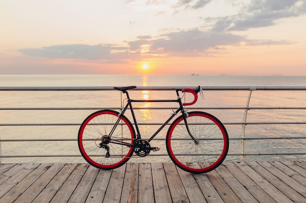 Hipster bicycle in morning sunrise by the sea