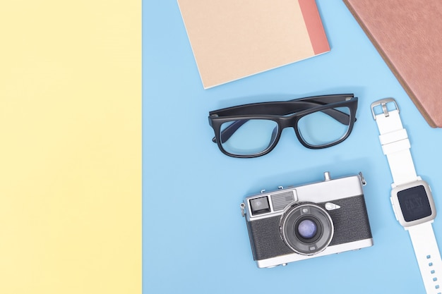 Hipster blogger travel objects on blue  pink yellow copy space for poster and banner
