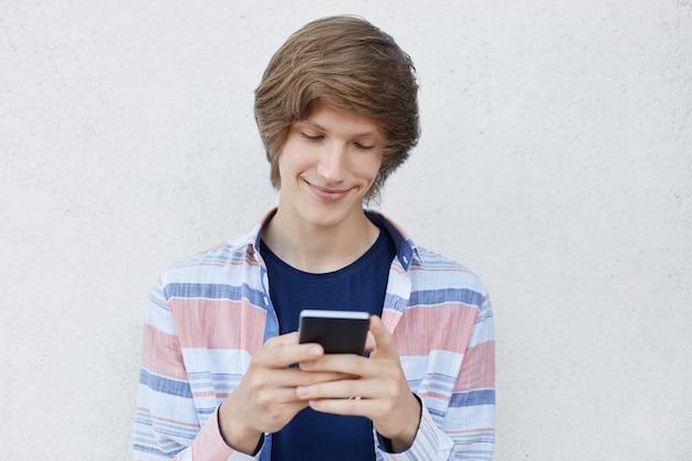 Мальчик-хипстер, держащий смартфон печатает сообщения своей подруге, радостно выражая свое мнение о своей любви