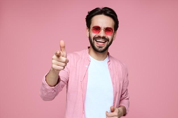 Хипстерский мальчик в розовой рубашке и солнцезащитных очках, улыбаясь на розовой стене