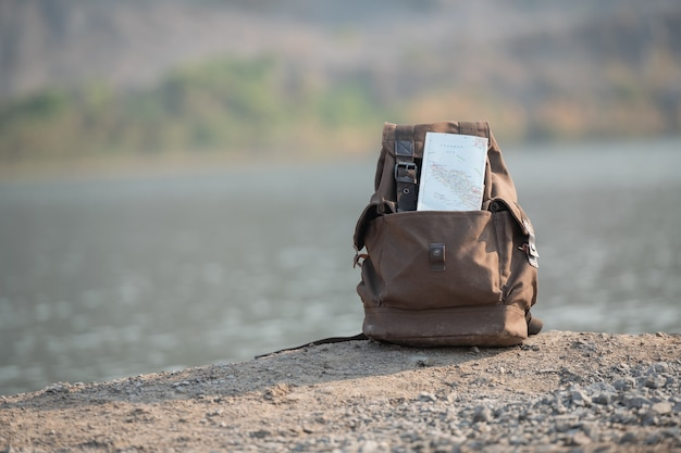 Hipster brown backpack and map close up. view from front tourist traveler bag