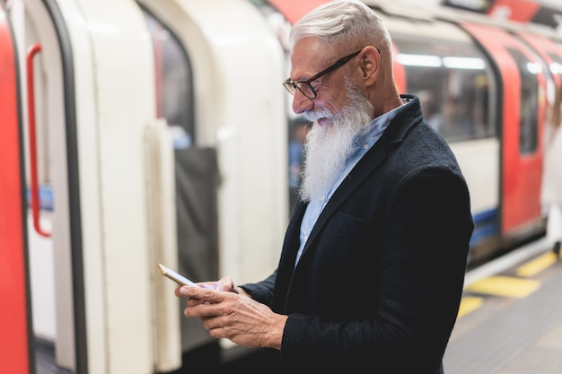 Hipster 비즈니스 수석 남자 지하철 역에서 휴대 전화를 사용하여-얼굴에 초점