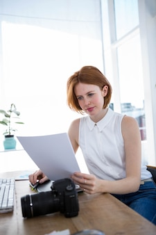 Hipster business woman sitting at her desk reading files