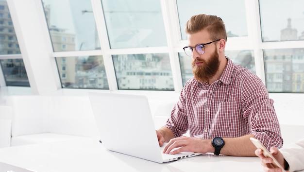 Битник бизнесмен в офисе, работая с ноутбуком со своей командой