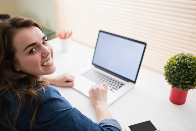 Hipster businesswoman using her laptop at her desk in office