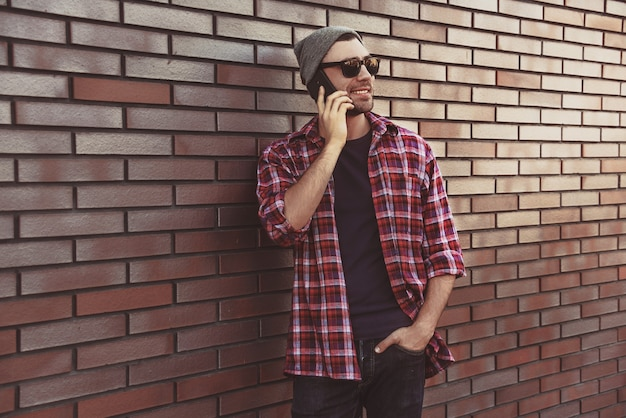 Hipster calling in city street on brick wall surface. amazing man holding smartphone in smart casual wear standing. urban young professional lifestyle.