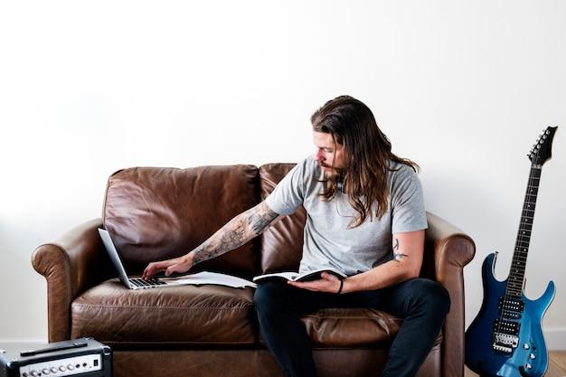 Hipster caucasian rocker working on a laptop