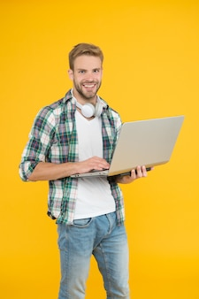 Hipster cheerful bearded face holding laptop. laptop computer repairman or tech worker. notebook for work and entertainment. guy enjoy modern technologies. use laptop with wireless headphones.