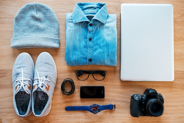 Hipster collection. top view of clothing and diverse personal accessory for hipster laying on the wooden grain