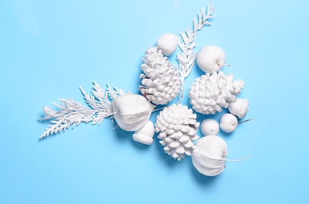 Хипстерский концептуальный минималистский фон рождество и новый год. шишки и ветки сосны, цветы физалиса. белые объекты на синем фоне с пространством для текста приветствия