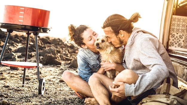 流行に敏感なカップルとかわいい犬がオールドタイマーのミニバン輸送で旅行でリラックス