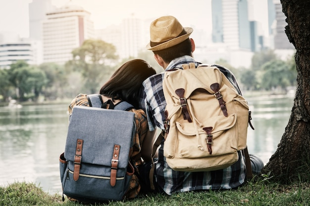 Hipster couple backpacking sitting under the tree on park, journey on holiday concept .