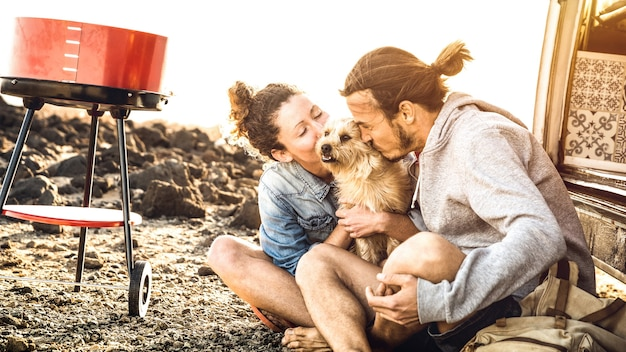 Hipster couple and cute dog relaxing by travel on oldtimer mini van transport