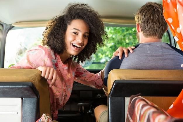 Hipster couple driving in camper van