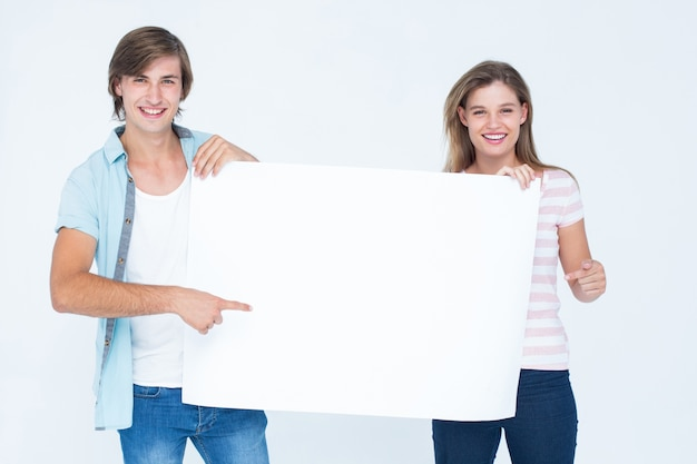 Hipster couple holding poster