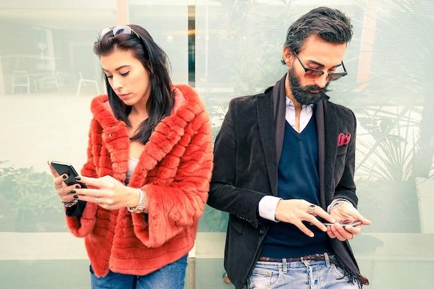 Хипстерская пара в грустный момент, игнорируя друг друга с помощью мобильных телефонов