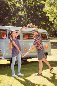 Hipster couple making heart with arms