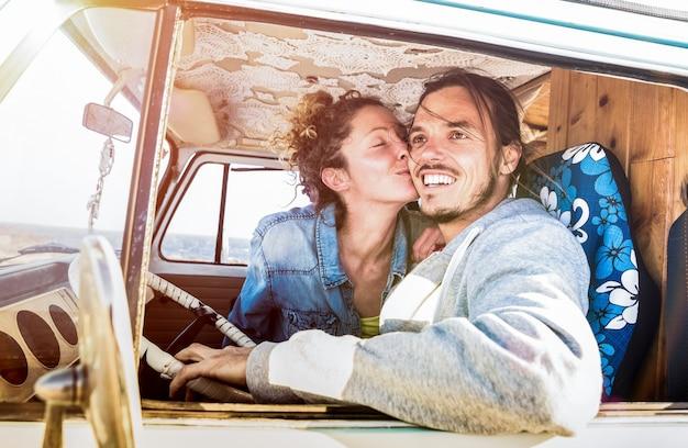 オールドタイマーミニバン輸送でロードトリップの準備ができている流行に敏感なカップル