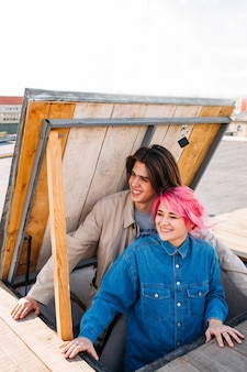 Hipster couple on the roof. happy pink hair girl and smiling long haired boy. teenage friendly or romantic relationship. exciting pastime