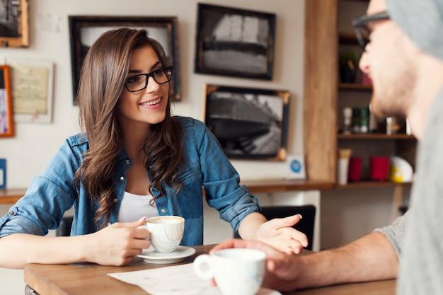 Coppia di hipster parlando al caffè