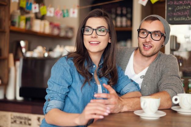 Coppia di hipster parlando con gli amici al caffè