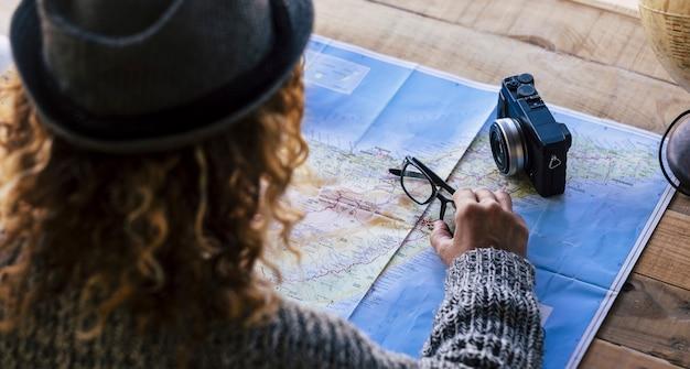 Hipster 곱슬 금발 여성은지도에 새로운 여행 vacatopon 방랑벽을 계획하는 후면에서 볼 수 있습니다. 네브라스카를 선택하고 꿈을 꿀 수있는 전 세계 구체가있는 나무 테이블에 안경과 카메라
