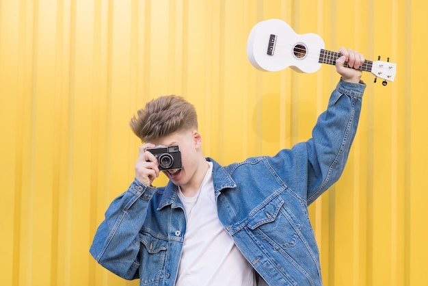 Hipster in a denim jacket holds ukulele in his hands and takes pictures on an old film camera.