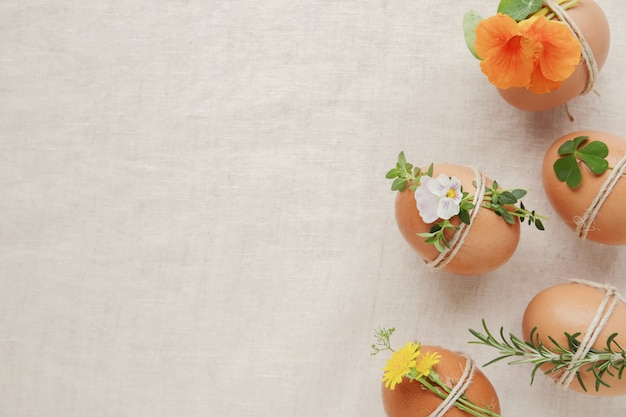 Hipster eco easter eggs with flowers and herbs on linen copy space background
