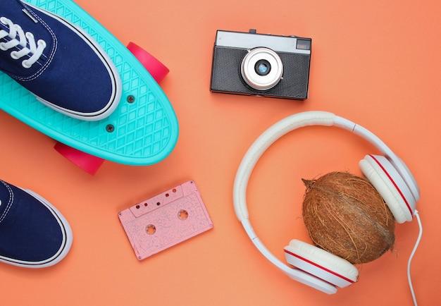 Хипстерский модный образ. скейтборд, кроссовки, ретро-камера, кокос с наушниками на фоне кораллового цвета. вид сверху. плоская планировка