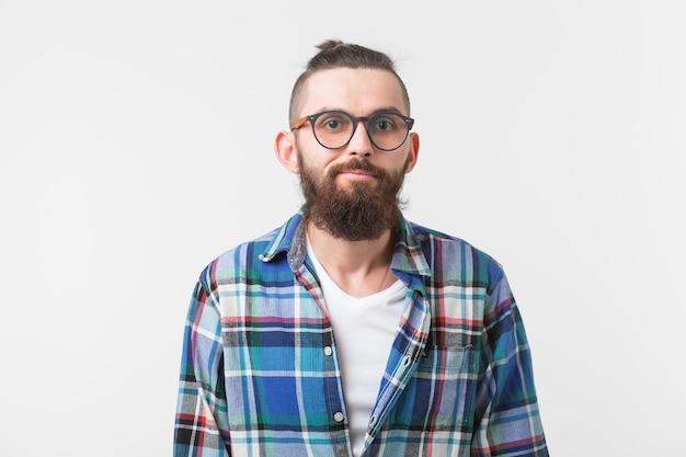 流行に敏感なファッションの人々は、眼鏡とシャツの上に立っている若い流行に敏感なひげを生やした男をコンセプトします