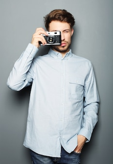 Hipster fashion photographer man holding retro camera