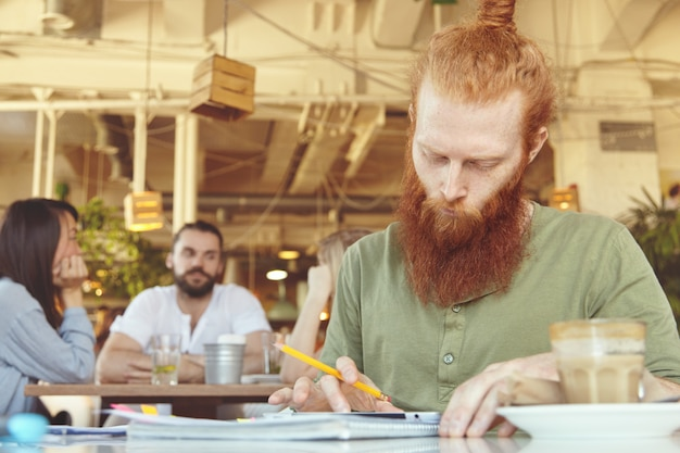 Hipster freelancer holding pencil, making notes in sheets of paper with graphics, using digital tablet for distant work at co-working space.