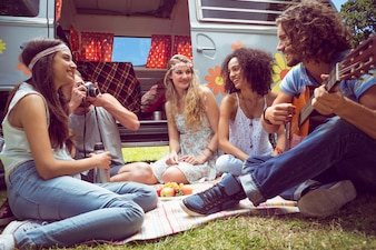 Hipster friends by camper van at festival