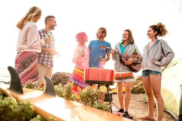 Хипстерские друзья веселятся на пляжной вечеринке в кемпинге