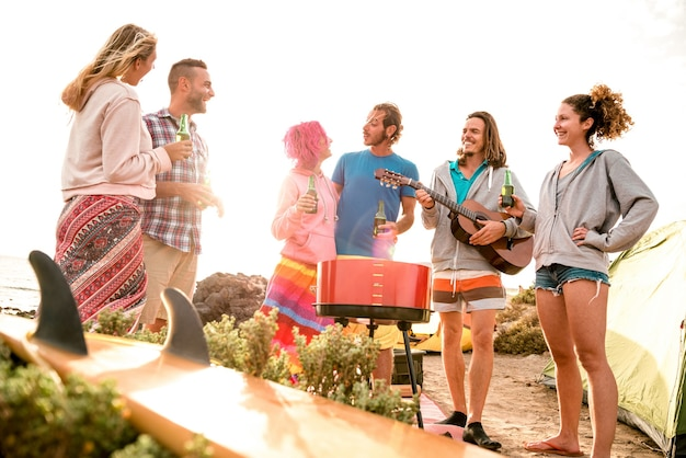 Hipster friends having fun at beach camping party